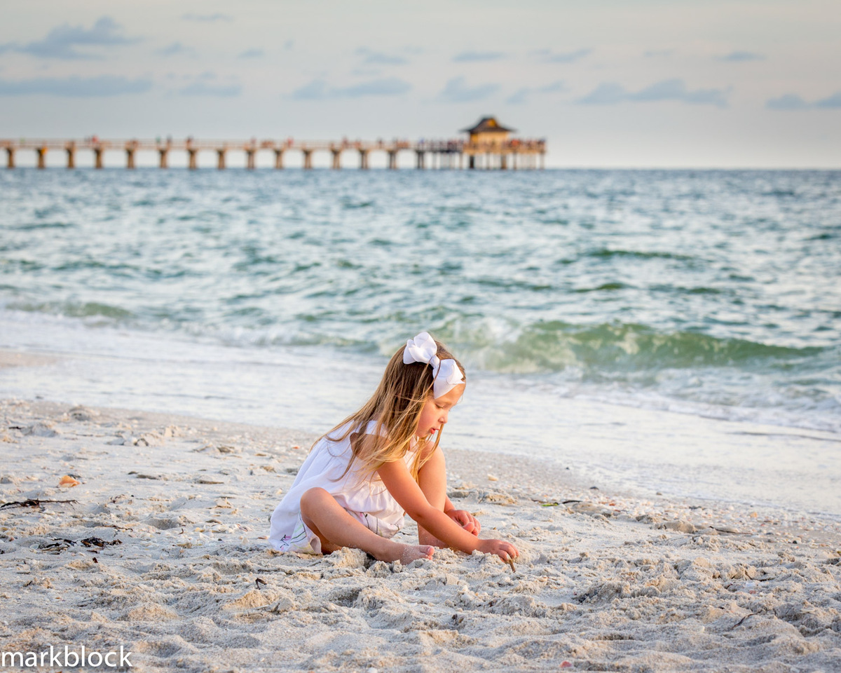 Photo of child sitting on beach with Naples Pier in background by Mark Block Photography